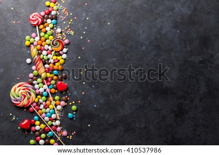 Colorful candies and lollipops over stone background. Top view with copy space