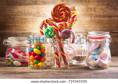 Colorful candies, jellies, lollipops, marshmallows and marmalade in a glass jars on wooden table