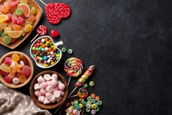 Colorful candies, jelly and marmalade on stone background. Top view with copy space