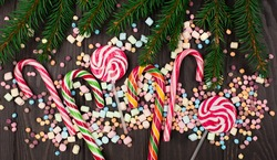 Colorful candies, lollypops, marshmallows, Candy canes and Fir Tree branches on dark wooden background. Top view, copy space. Holiday Christmas sweet concept.