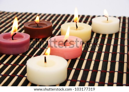 Colorful candles on bamboo background.