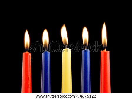 Colorful candles on black background