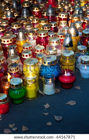 Colorful candles on cemetery during Halloween holiday