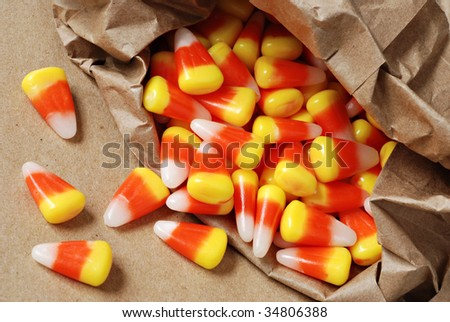 Colorful candy corn spilling from brown paper bag.  Macro with shallow dof.
