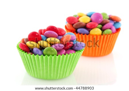 colorful candy in paper cup cake papers isolated over white