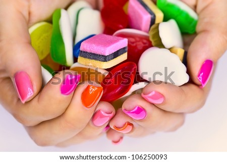 Colorful candy in the hands of women