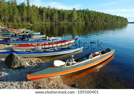 Colorful canoes on a sand bank of Engozero lake,Polar Karelia, Russia - stock photo