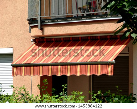 colorful canvas awning in yellow & orange. canopy over residential balcony. sunny summer day. sun protection concept. UV exposure. warm color waterproof fabric material. green garden. selective focus. #1453884122