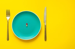 Colorful capsule on plate on yellow background with copy space. Health care or synthetic food concept. Top view. Antipyretic tablet. Coronavirus.