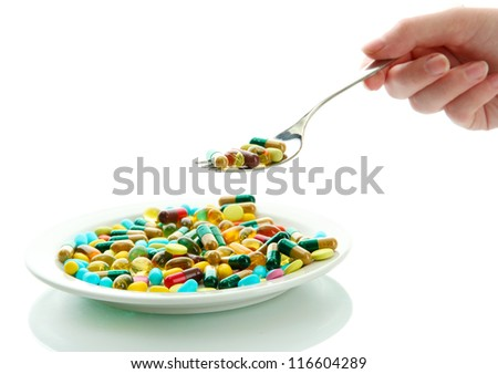 Colorful capsules and pills on plate with spoon in hand, close up