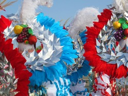 Colorful carnival background with fruit headdresses and shiny feathers. Dancers in festival costumes who celebrate Carnival on the streets. Fantasy headdresses pattern.