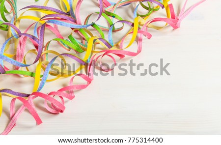Colorful carnival serpentines on white wooden background, top niew, copy space