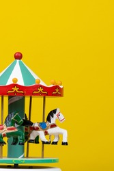 colorful carousel toy in yellow background. Vertical