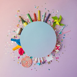 Colorful celebration background with various party confetti, balloons, streamers, fireworks and decoration on pink background. Flat lay.