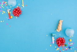 Colorful celebration pattern with various party confetti, balloons and red bows on blue background. Flat lay