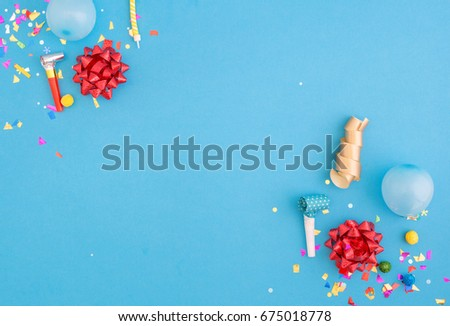 Colorful celebration pattern with various party confetti, balloons and red bows on blue background. Flat lay #675018778