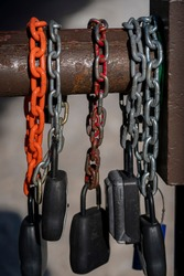 Colorful chains and locks hang on a rusted steel gate at a forest service road in the mountains.