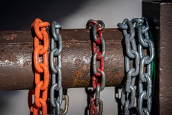 Colorful chains hang on a rusted steel gate at a forest service road in the mountains.