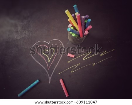 Colorful chalk in steel box with drawing cartoon heart on the black background. #609111047