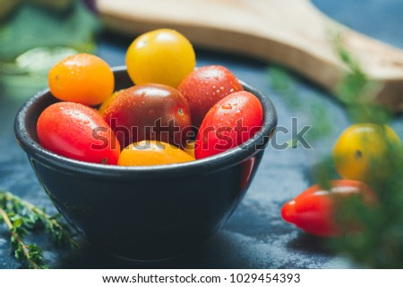 Colorful cherry tomatoes in a black bowl in a kitchen. #1029454393