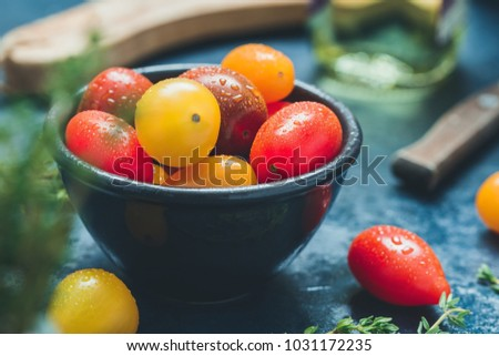 Colorful cherry tomatoes in a black bowl in a kitchen. #1031172235