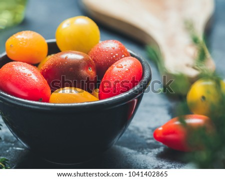 Colorful cherry tomatoes in a black bowl in a kitchen. #1041402865