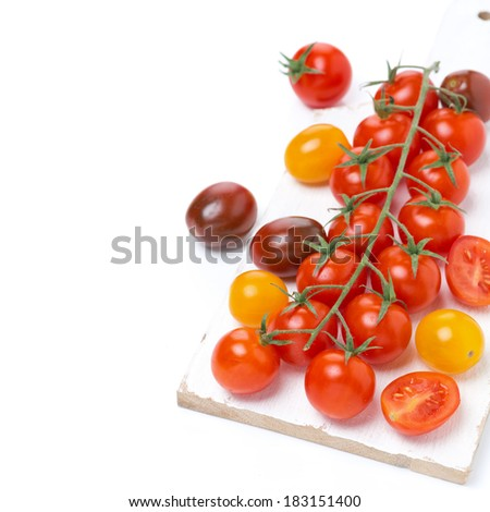 colorful cherry tomatoes on a white wooden board, top view, isolated on white