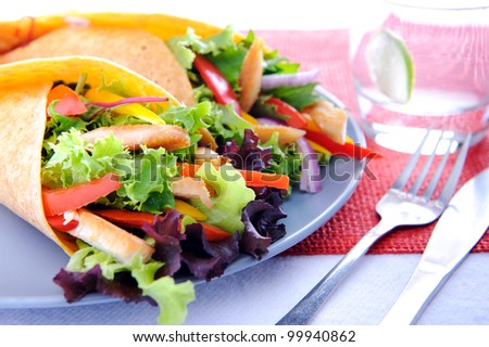 Colorful chicken wrap with plenty of fresh salad and a set of cutlery - stock photo