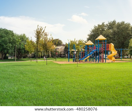 Colorful children playground activities in public park surrounded by green trees at sunset in Houston, Texas. Children run, slide, swing on modern playground. Urban neighborhood childhood concept. #480258076