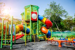 Colorful children playground,exercise kid,activities in outdoor public park surrounded by green trees at sunlight morning.Children run, slide,seesaw on modern playground.Funny toy land for child