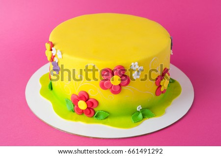Colorful children's birthday cake made of yellow mastic decorated with pink flowers, leaves, pattern on a pink background. Close-up. Cutout. Picture for a menu or a confectionery catalog.