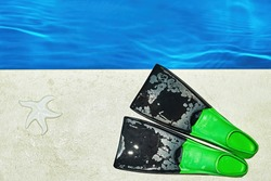 Colorful children's flippers and starfish on the tiles at the edge of the pool. Snorkeling and outdoor activities