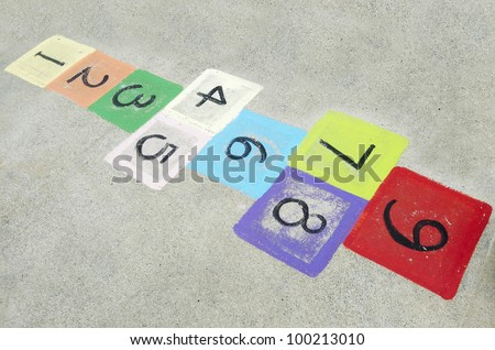 Colorful children's hopscotch on playground concrete. Concept photo of child, childhood, young, outdoor, game , memory, nostalgia, kindergarten, past,sentimentality.