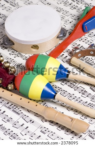 Colorful children\'s instruments laying on top of a complicated musical score