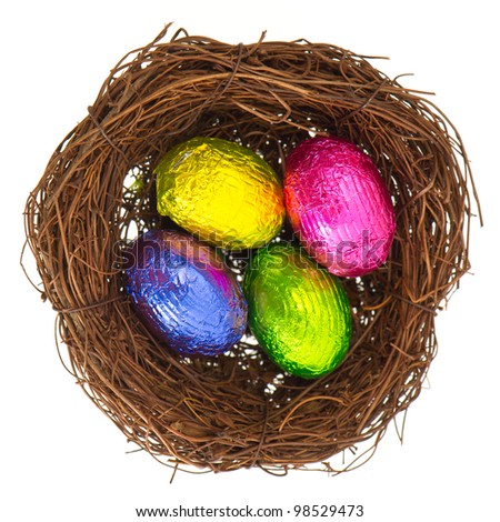 colorful chocolate easter eggs in nest on white background