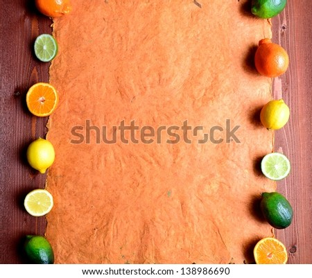 Colorful citrus fruits.frame.on brown wood background