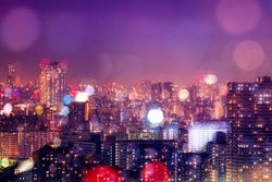 Colorful city buildings nightlife background decorated with de-focus bokeh lights reflecting from the buildings and purple filter. The dense Asian-style buildings were taken in Tokyo, Japan.