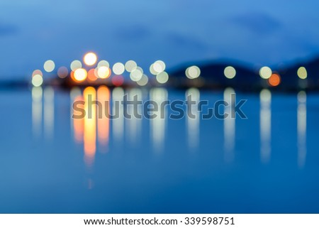 Colorful city lights with bokeh effect reflected over sea  background at dusk #339598751