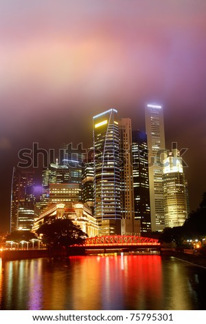 Colorful city night scene with skyscrapers near river in Singapore, Asia.