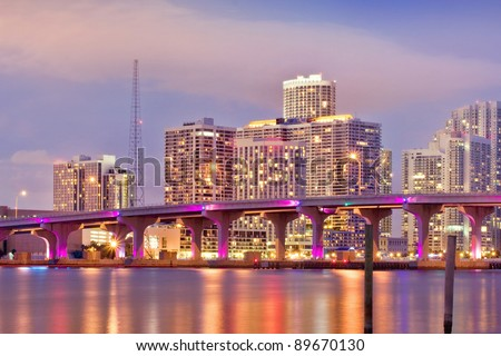 Colorful Cityscape of Miami Florida, downtown buildings and MacArthur Causeway bridge illuminating Biscayne bay at sunset.