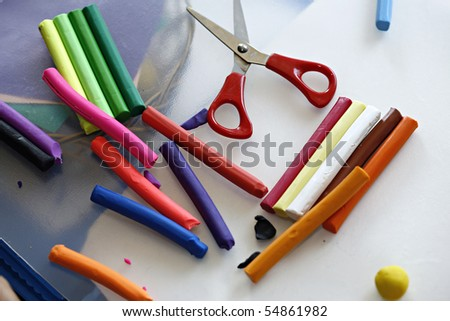 Colorful clay dough (plasticine) and scissors
