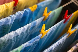 Colorful clean bed linen and towels after washing are hung on the bars of the dryer and secured with clothespins. General cleaning, Laundry drying, compact dryer for the house. Selective focus