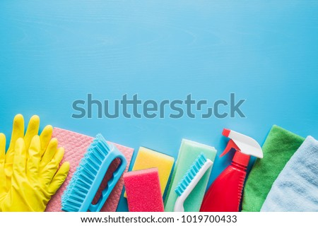Colorful cleaning set for different surfaces in kitchen, bathroom and other rooms. Empty place for text or logo on blue background. Cleaning service concept. Early spring regular clean up.