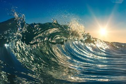 Colorful clear ocean wave closing. Shorebreak shot in open water. Bright sun rising over seascape. Marine environment natural background