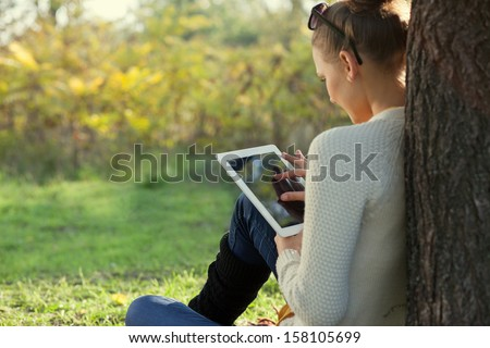Colorful Close Up of using tablet in the park.