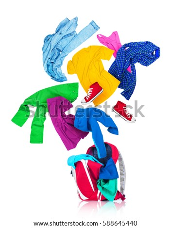 Colorful clothes are falling in a red backpack isolated on white