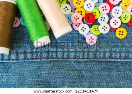 colorful clothes buttons for sewing with thread spool on jeans fabric in top view #1211411479