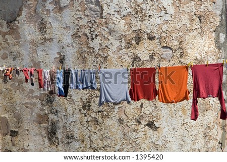 Colorful clothes drying by an old wall