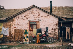 Colorful clothes hanging on the rope with an old red motorcycle on the background next to the wall of an abandoned house with a broken window