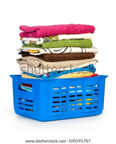 Colorful clothes in a laundry basket on white background.